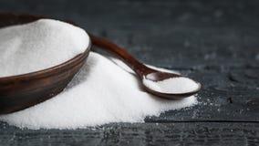 有白海盐和木匙子的黏土碗在桌上 免版税库存照片