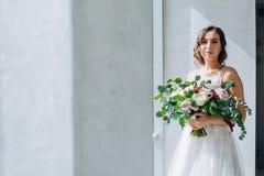 有白玫瑰婚姻的花束的新娘在手上 免版税库存照片