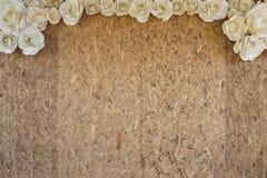 有白皮书玫瑰色花框架的老木颗粒盘 免版税库存图片