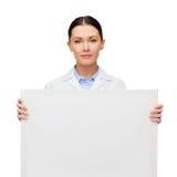 有白空白的委员会的镇静女性医生 免版税库存图片