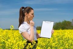 有白纸文件的女孩在黄色花田 库存照片
