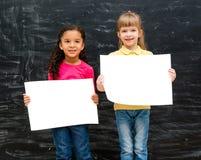 有白纸的两个相当小女孩在手上 库存照片