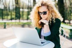 有白肤金发的卷发佩带的坐在开放膝上型计算机户外读前面的太阳镜和典雅的高尔夫球外套的少妇新 免版税库存图片