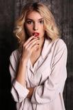 有白肤金发的卷发和晚上构成的美丽的妇女,穿白色衬衣 免版税库存图片