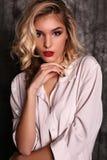 有白肤金发的卷发和晚上构成的美丽的妇女,穿白色衬衣 免版税库存照片
