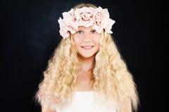有白肤金发的卷发和花的美丽的青少年的女孩在黑暗 免版税库存图片