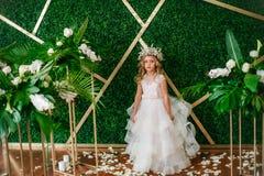 有白肤金发的卷发在一套白色婚礼礼服和花花圈的逗人喜爱的小女孩在花卉装饰的 免版税图库摄影