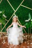 有白肤金发的卷发在一套白色婚礼礼服和花花圈的逗人喜爱的小女孩在花卉装饰的 图库摄影