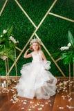 有白肤金发的卷发在一套白色婚礼礼服和花花圈的逗人喜爱的小女孩在花卉装饰的 库存图片
