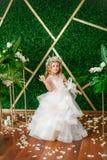有白肤金发的卷发在一套白色婚礼礼服和花花圈的逗人喜爱的小女孩在花卉装饰的 免版税库存图片