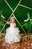 有白肤金发的卷发在一套白色婚礼礼服和花花圈的逗人喜爱的小女孩在花卉装饰的 库存照片