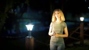 有白肤金发的卷发的一名苗条甜妇女,中年,在街道上的夏天晚上晚了站立在明亮附近 影视素材