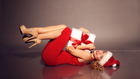 有白肤金发的卷发的少妇穿圣诞老人帽子和典雅的红色礼服 图库摄影