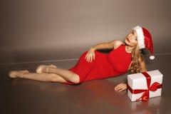 有白肤金发的卷发的少妇穿圣诞老人帽子和典雅的红色礼服 免版税库存照片