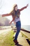 有白肤金发的卷发的微笑的妇女在晴朗的背景 图库摄影