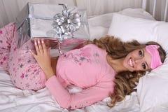 有白肤金发的卷发的性感的美丽的妇女在有礼物的睡衣 免版税库存图片