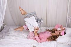 有白肤金发的卷发的性感的美丽的妇女在有礼物的睡衣 免版税库存照片