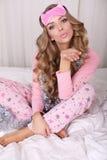 有白肤金发的卷发的性感的美丽的妇女在睡衣 免版税图库摄影