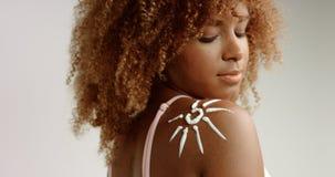 有白肤金发的卷发的混合的族种黑人妇女在有奶油的演播室在她的皮肤 免版税库存图片