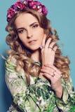 有白肤金发的卷发的美丽的少妇,佩带典雅的衣裳和珠宝, 免版税图库摄影