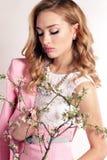 有白肤金发的卷发的美丽的少妇,佩带典雅的衣裳和珠宝, 免版税库存照片