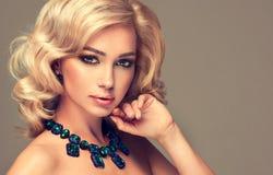 有白肤金发的卷发的美丽的逗人喜爱的女孩 免版税库存照片