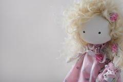 有白肤金发的卷曲头发特写镜头的逗人喜爱的手工制造玩偶与copyspace 免版税库存照片