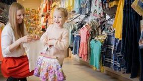 有白肤金发的女儿买的孩子的年轻母亲在商店穿衣 库存照片