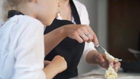 有白肤金发的女儿的少妇在早晨厨房做酸奶干酪薄煎饼 股票录像