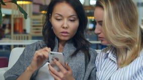 有白肤金发的朋友的愉快的购物的亚洲妇女用途智能手机商城的 图库摄影