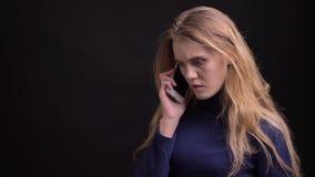 有白肤金发的模型在哀伤地观看入在黑背景的照相机的智能手机的一严肃的voicecall 股票视频