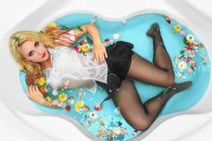 有白肤金发的湿头发、明亮的构成和湿白色在浴缸的女衬衫和黑微型裙子的性感的热情的可爱的女孩 库存照片