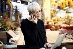 有白肤金发的短发的年轻俏丽的行家妇女坐台阶,谈话由研究膝上型计算机的手机 免版税库存照片
