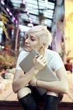有白肤金发的短发的年轻行家妇女坐台阶,拿着现代便携式计算机 库存图片