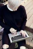 有白肤金发的短发的年轻行家妇女坐台阶,研究现代便携式计算机,看得下来,感人的键盘 免版税库存照片