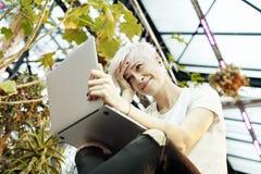 有白肤金发的短发的年轻行家妇女微笑和研究便携式的便携式计算机的,坐台阶 室内植物的ga 免版税库存照片