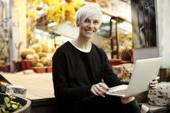 有白肤金发的短发的年轻行家妇女微笑和研究膝上型计算机的,坐台阶 室内植物园内部 库存照片
