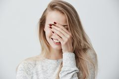 有白肤金发的长的头发的,闭合值的眼睛悦目情感年轻白种人妇女用手,当大声时笑  免版税库存图片