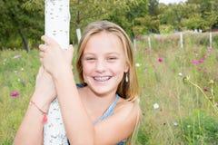 有白肤金发的长的站立在绿色前面的头发和大蓝眼睛的十几岁的女孩 库存照片