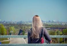 有白肤金发的长的头发的妇女观察都市风景 库存图片