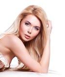 有白肤金发的长的头发的美丽的妇女用在面孔附近的手 免版税库存图片