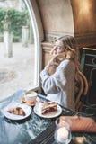 有白肤金发的长的头发的美丽的少妇花费与h的时间 免版税图库摄影