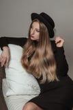 有白肤金发的长的头发的美丽的时髦的妇女在黑礼服和帽子 免版税库存图片