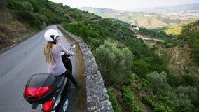 有白肤金发的dreadlocks的少妇在杜罗河谷,葡萄牙的一辆摩托车旅行 库存图片
