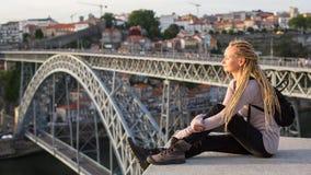 有白肤金发的dreadlocks的少妇在Dom我横跨杜罗河河跨接的雷斯对面的观察平台 免版税库存照片