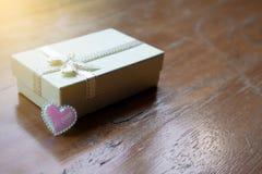 有白色丝带和桃红色闪闪发光微小的心脏的特写镜头小白色peatl礼物盒 免版税库存照片
