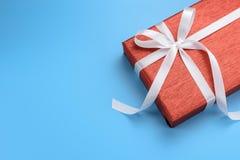 有白色丝带的红色礼物盒在蓝色背景 免版税库存照片