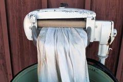有白色亚麻布的绞扭机洗衣机 免版税库存图片