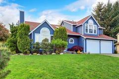 有白色修剪和好的草坪的大蓝色房子 库存照片
