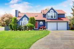 有白色修剪和好的草坪的大蓝色房子 免版税库存照片